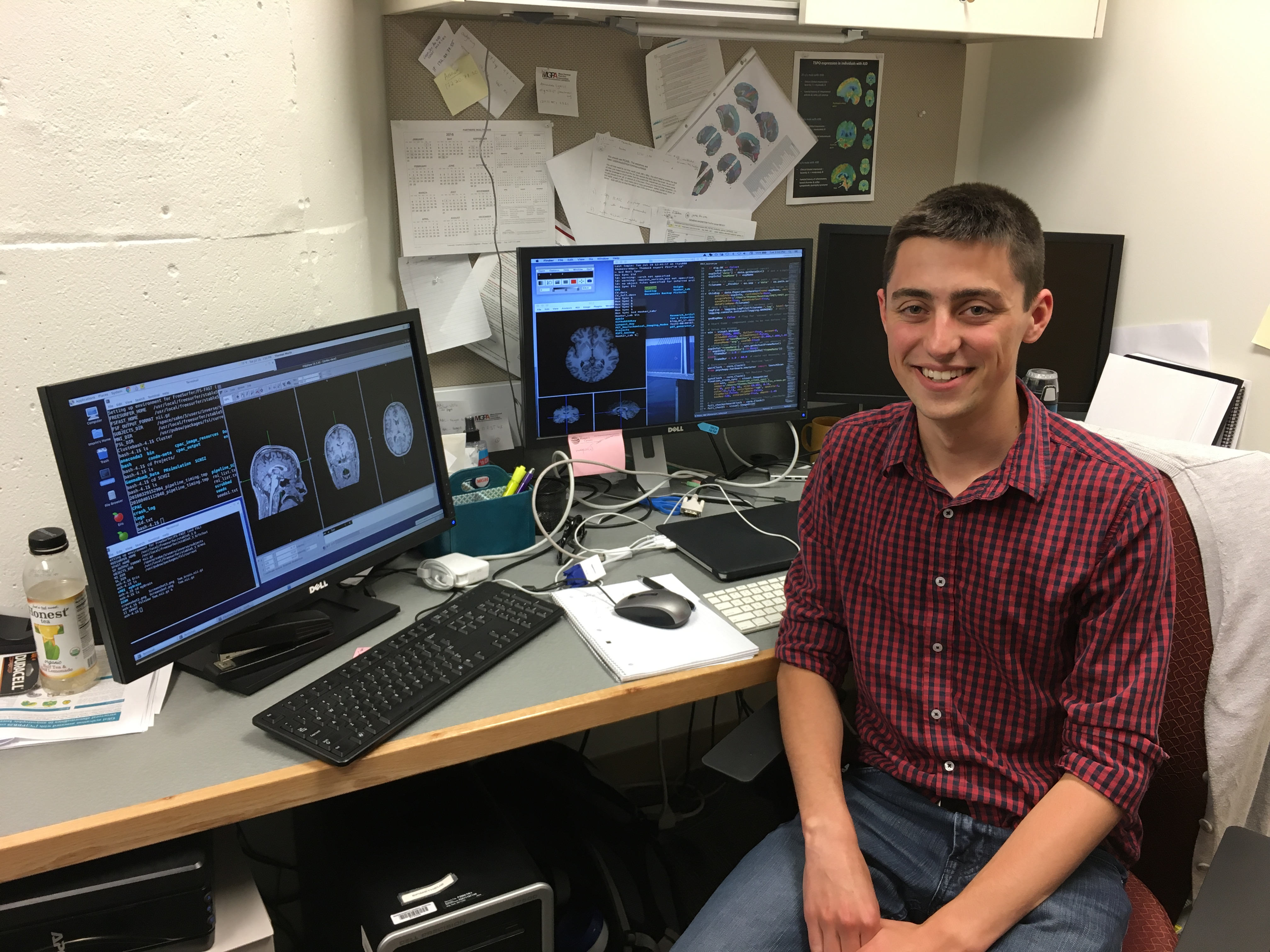 Me sitting in front of a computer in the lab I used to work at with some brain images opened up